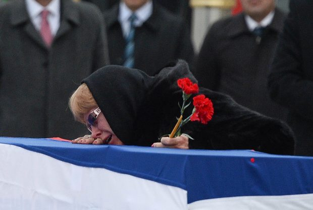 ANKARA, TURKEY - DECEMBER 20: Marina Karlov mourns her husband laying her head on top a flag-wrapped coffin of late Russian Ambassador to Turkey Andrei Karlov before being carried to a plane by Turkish soldiers during a ceremony at Esenboga airport on December 20, 2016 in Ankara. Turkey. Russia's ambassador to Turkey, Andrey Karlov, was shot dead by a Turkish policeman shouting 'Don't forget Aleppo! Don't forget Syria' at an art exhibition in the Turkish capital of Ankara yesterday. (Photo by Erhan Ortac/Getty Images)