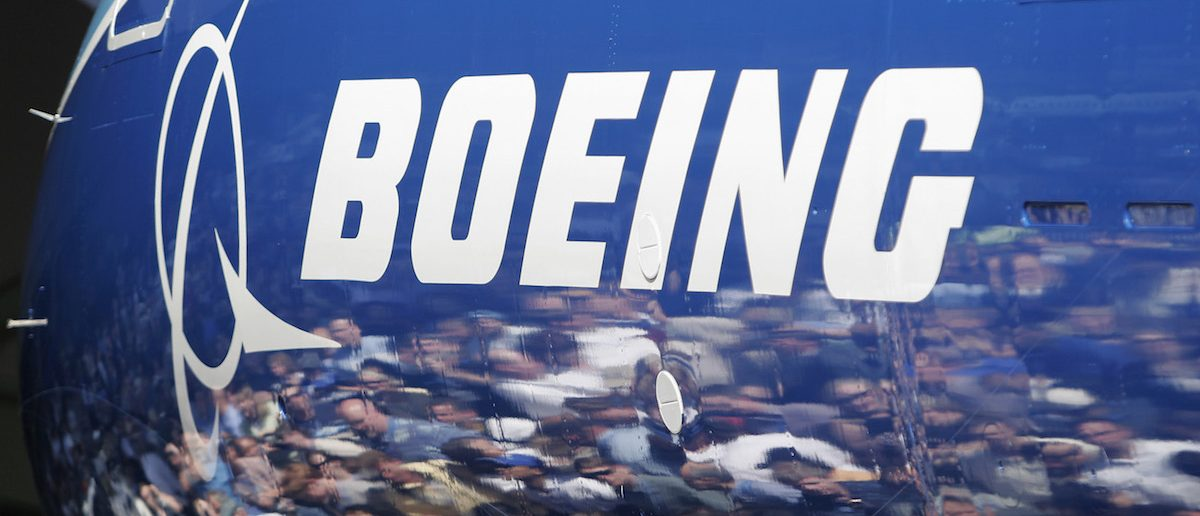 Invited guests for the world premiere of the Boeing 787 Dreamliner are reflected in the fuselage of the aircraft at the 787 assembly plant in Everett, Washington, July 8, 2007. REUTERS/Robert Sorbo (UNITED STATES) - RTR1RMUL