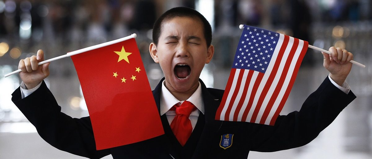 A boy who is waiting to greet U.S. Secretary of State Hillary Clinton at the National Museum makes a face while holding the U.S. and Chinese flags in Beijing May 4, 2012. REUTERS/Shannon Stapleton