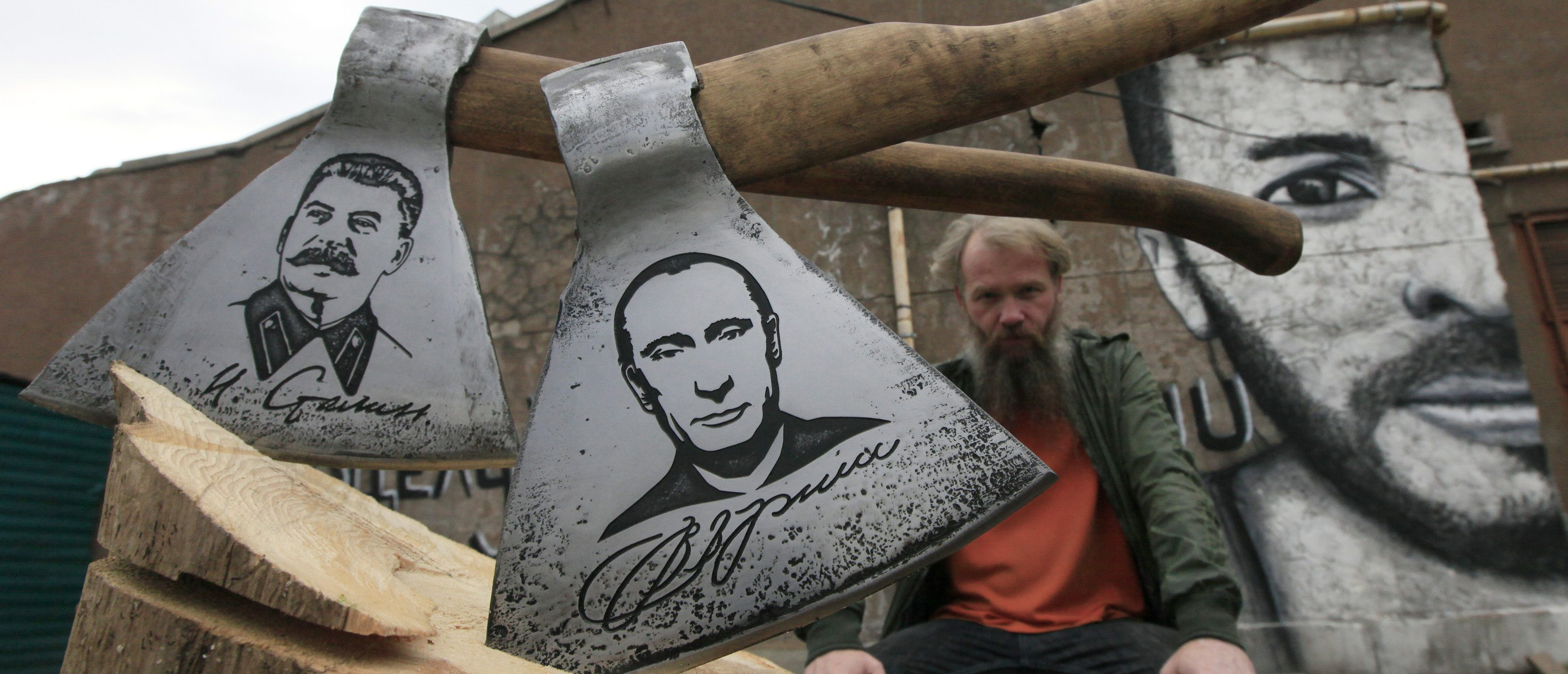 """Russian artist Vasily Slonov poses for a picture with axes engraved with portraits of Russian President Vladimir Putin and Soviet leader Josef Stalin, during a presentation of his new art project """"History of Russia, 20th century - from Lenin to Putin"""" at the courtyard of the Museum Center in Russia's Siberian city of Krasnoyarsk September 2, 2013. The artist has chemically engraved portraits of nine Soviet and Russian political figures on a series of butchers' axes.  REUTERS/Ilya Naymushin"""