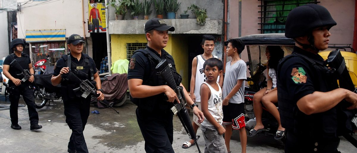 Members of Philippine National Police's SWAT team hold their weapons as they walk past residents during an anti-drugs operation in Mandaluyong, Metro Manila in the Philippines, November 10, 2016. REUTERS/Erik De Castro
