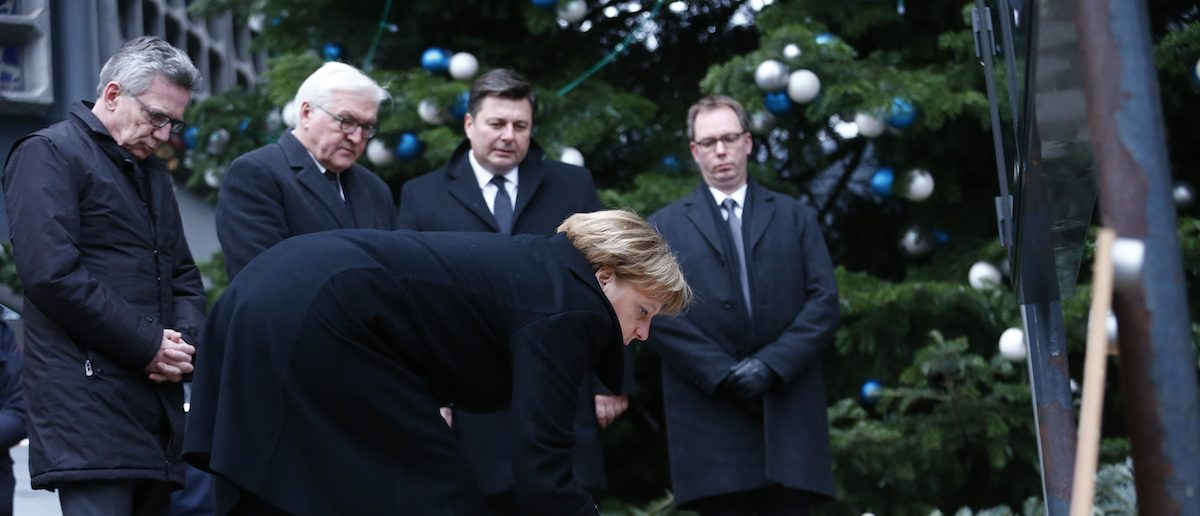 German Chancellor Angela Merkel lays flowers at the Christmas market in Berlin, Germany, December 20, 2016, one day after a truck ploughed into a crowded Christmas market in the German capital.       REUTERS/Hannibal Hanschke - RTX2VV7K