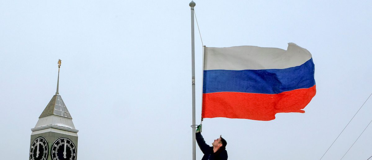 A worker lowers the Russian national flag to half-mast on a roof of the city administration building, as the country observes a day of mourning for victims of the Tu-154 plane which crashed into the Black Sea on its way to Syria on Sunday, in Krasnoyarsk, Russia, December 26, 2016.  REUTERS/Ilya Naymushin     TPX IMAGES OF THE DAY - RTX2WGWU
