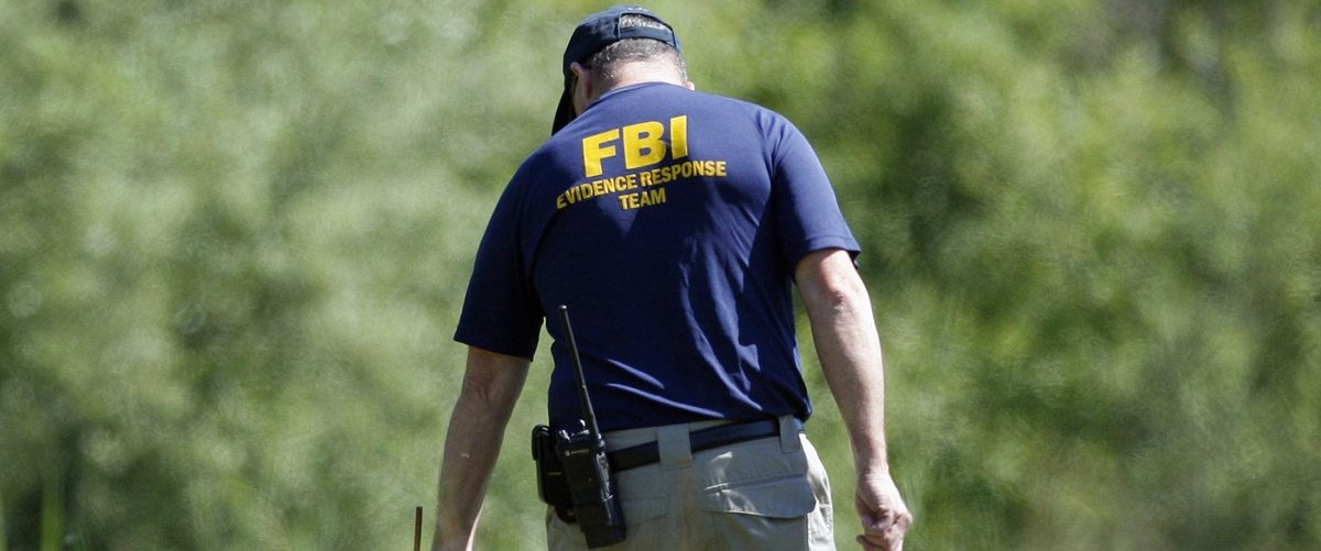 A federal agent stretches yellow crime tape across a field for Hoffa investigation in Oakland Township, Michigan