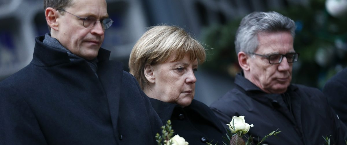 Berlin mayor Michael Mueller, German Chancellor Angela Merkel and German interior minister Thomas de Maiziere stand in silence at the Christmas market in Berlin, Germany, December 20, 2016, one day after a truck ploughed into a crowded Christmas market in the German capital.       REUTERS/Hannibal Hanschke.