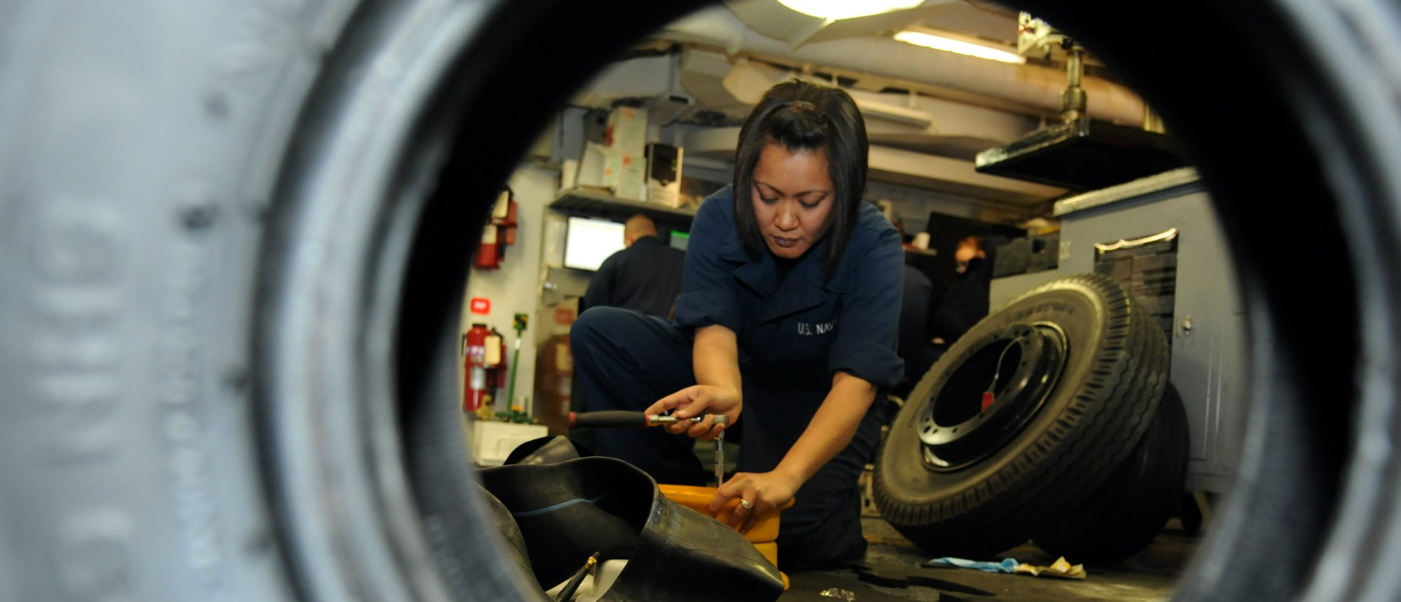 Aviation Support Equipment Technician Airman Gladys J. Domingo, assigned to the aviation intermediate maintenance department aboard the aircraft carrier USS George H.W. Bush (CVN 77), assembles a front tire for an aircraft tow tractor.  (U.S. Navy photo by Mass Communication Specialist Seaman Billy Ho/Released)