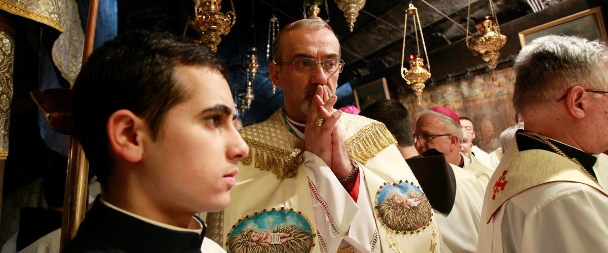 The Latin Patriarch of Jerusalem Pierbattista Pizzaballa prays in the Grotto during a Christmas midnight mass at the Church of the Nativity in the West Bank town of Bethlehem