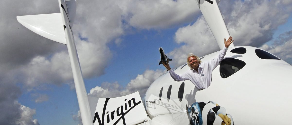 Entrepreneur Richard Branson waves a model of the LauncherOne cargo spacecraft from a window of an actual size model of SpaceShipTwo on display, after Virgin Galactic's LauncherOne announcement and news conference, at the Farnborough Airshow 2012 in southern England July 11, 2012. (REUTERS/Luke MacGregor)