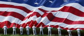 U.S. sailors unravel a huge American flag across the field during opening day ceremonies before the San Diego Padres host the Los Angeles Dodgers in their MLB National League baseball game in San Diego
