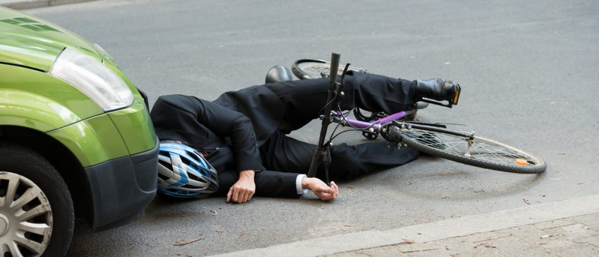 Unconscious Male Cyclist Lying On Road After Accident [Shutterstock - Andrey_Popov]
