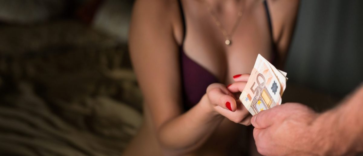 Woman taking money for her service. [Shutterstock - Kaspars Grinvalds]