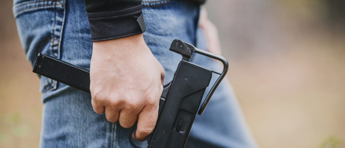 Man in jeans holding a submachine gun (Photo via Shutterstock)