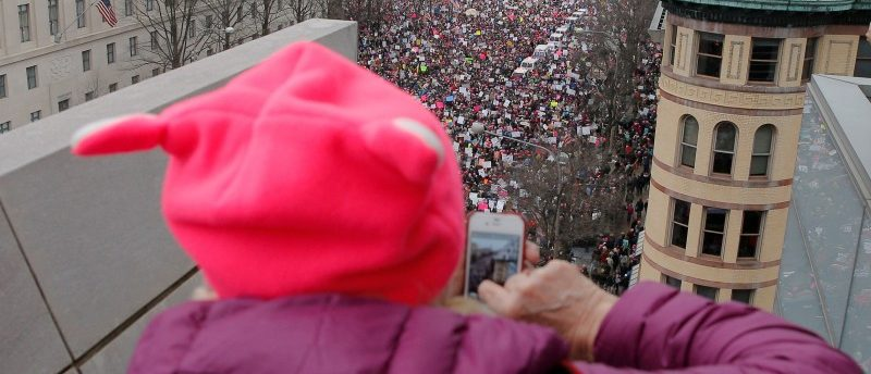 A woman wearing a pink pussy protest hat takes a photograph of the Women's March on Washington. REUTERS/Brian Snyder