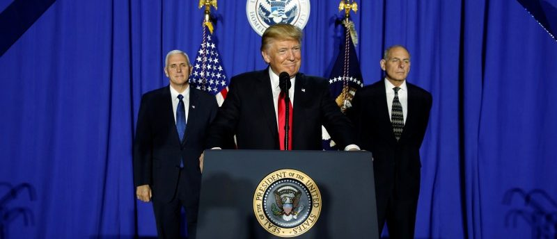 President Donald Trump (C), flanked by Vice President Mike Pence (L) and Homeland Security Secretary John Kelly (R), takes the stage to deliver remarks at Homeland Security headquarters in Washington. REUTERS/Jonathan Ernst