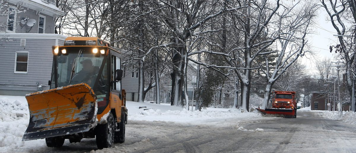A sidewalk plow and a street plow work to clear a neighborhood in Bangor, Maine, December 30, 2016. REUTERS/Ashley Conti