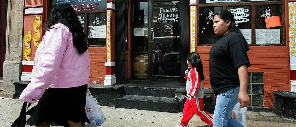 """CHICAGO - MAY 02: Pedestrians walk past the Fogata Village restaurant in Pilsen, a largely Hispanic neighborhood, on May 2, 2006 in Chicago, Illinois. The Fogata Village restaurant reopened today after closing yesterday in support of """"National Day of Mobilization"""" activities for immigrants' rights. (Photo by Tim Boyle/Getty Images)"""