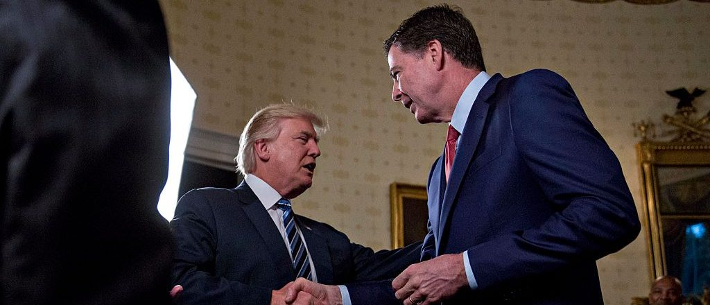 "WASHINGTON, DC - JANUARY 22: U.S. President Donald Trump (C) shakes hands with James Comey, director of the Federal Bureau of Investigation (FBI), during an Inaugural Law Enforcement Officers and First Responders Reception in the Blue Room of the White House on January 22, 2017 in Washington, DC. Trump today mocked protesters who gathered for large demonstrations across the U.S. and the world on Saturday to signal discontent with his leadership, but later offered a more conciliatory tone, saying he recognized such marches as a ""hallmark of our democracy."" (Photo by Andrew Harrer-Pool/Getty Images)"