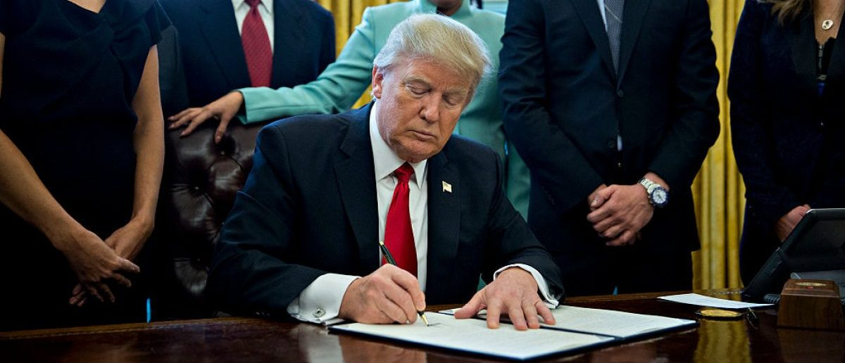 WASHINGTON, DC - JANUARY 30: U.S. President Donald Trump signs an executive order in the Oval Office of the White House. (Photo by Andrew Harrer - Pool/Getty Images)