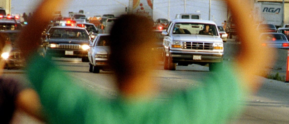 A man cheers as the Ford Bronco carrying OJ Simpson (R) is chased by dozens of police cars during a pursuit through Los Angeles area freeways, June 17, 1994. Sam Mircovich/Reuters)
