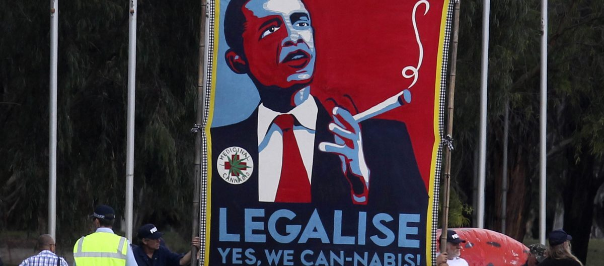 Protesters hold giant sign to legalize marijuana before U.S. President Barack Obama arrives to participate in an official arrival ceremony at Parliment House in Canberra, Australia, November 16, 2011. REUTERS/Larry Downing