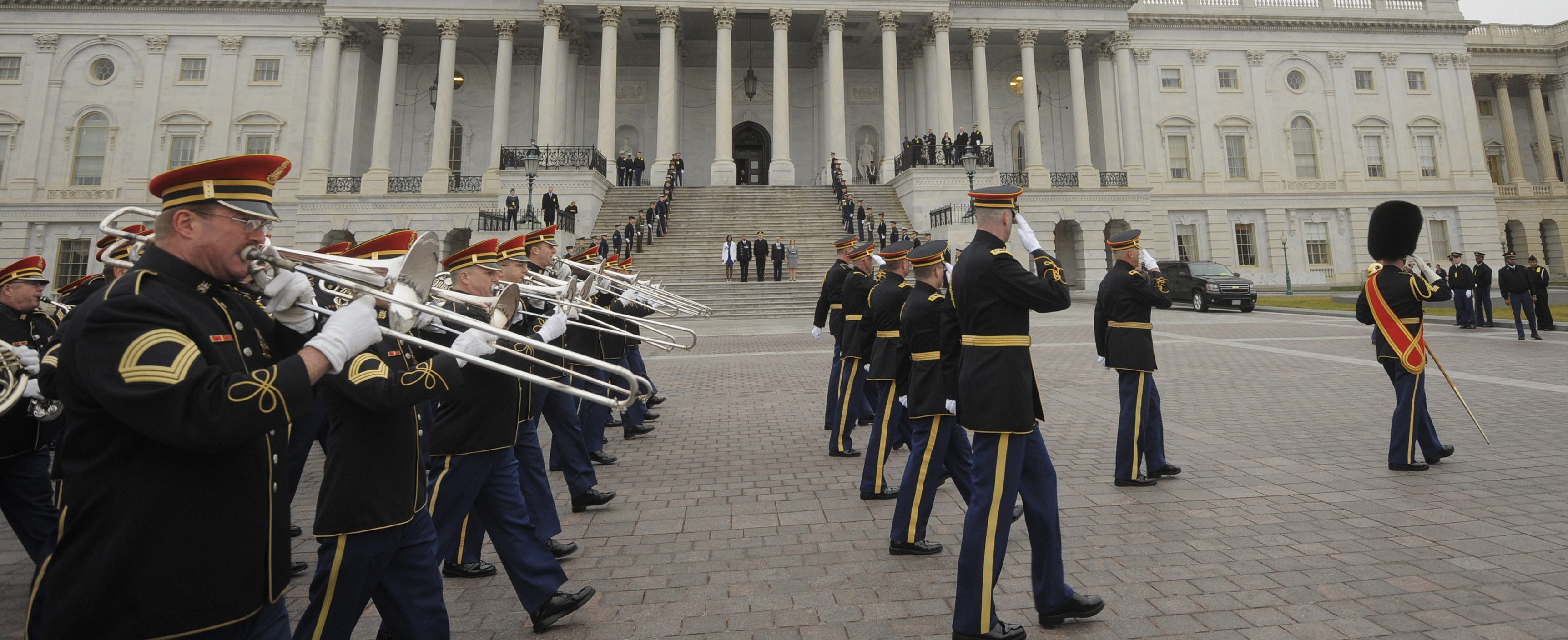 Members of the military band pass actors portraying (C, on steps) U.S. President Barack Obama, First Lady Michelle Obama, Vice President Joe Biden and his wife Jill Biden as they perform during a dress rehearsal at the U.S. Capitol in Washington January 13, 2013. The official inauguration and swearing-in will take place on January 21, 2013. REUTERS/Mike Theiler (UNITED STATES - Tags: POLITICS) - RTR3CE4R