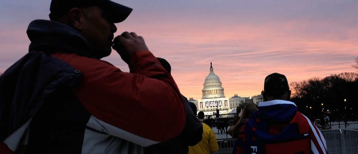 A Trump supporter takes a drag of a cigarette as the sun begins to rise over the U.S. Capitol on the National Mall before President-elect Donald Trump is to be sworn in in Washington, January 20, 2017. REUTERS/James Lawler Duggan