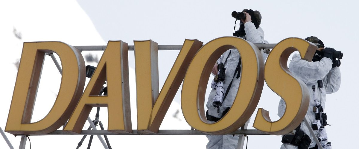 Swiss special police officers observe the surrounding area from atop the roof of Davos Congress Hotel in Davos