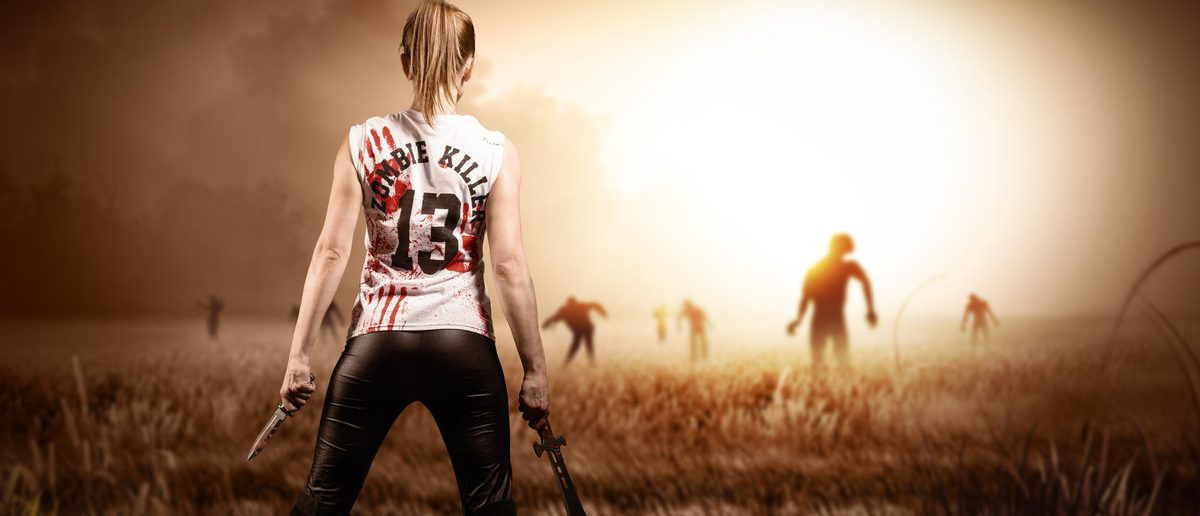 scene like in a horror movie with a woman holding a machete and a knife and standing on a field with approaching zombies (Shutterstock.com/fotogestoeber)