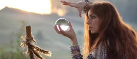 Psychic witch with crystal ball at sunset (Shutterstock/alexkich)
