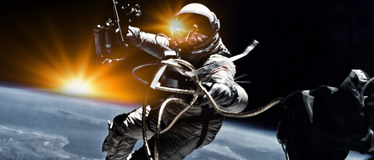 Astronaut on space mission with sun and earth on the background. Elements of this image furnished by NASA.  (Shutterstock.com/Bakhur Nick)