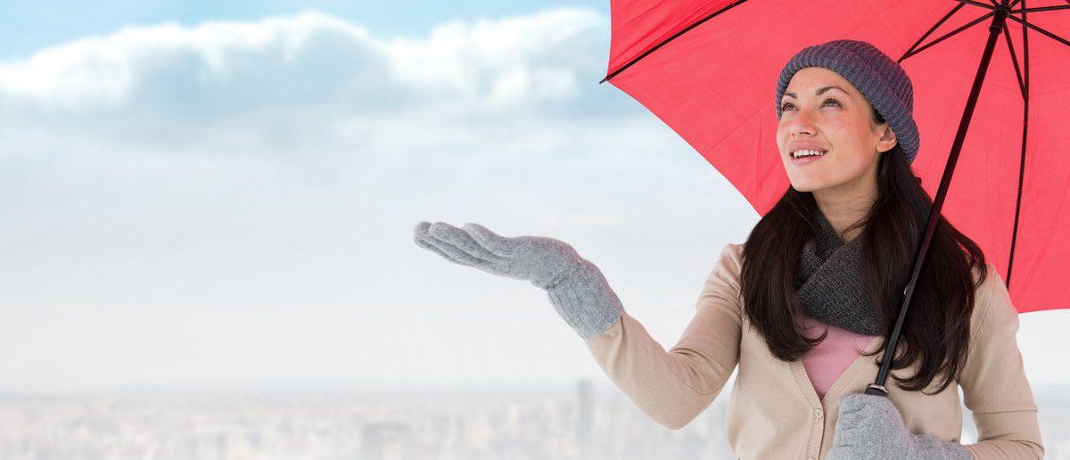 Smiling brunette feeling the rain against balcony overlooking city (Shutterstock.com/vectorfusionart)