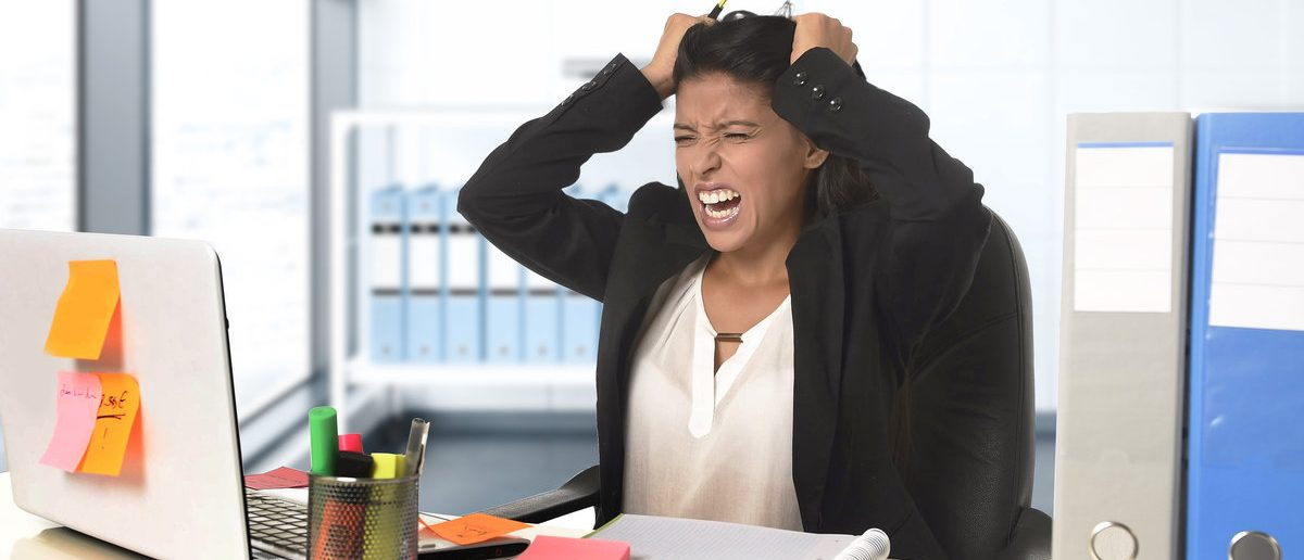 Young beautiful latin businesswoman suffering stress working at modern office computer desk looking worried and desperate having problem pulling her hair at work in overwork concept (Shutterstock/ Marcos Mesa Sam Wordley)