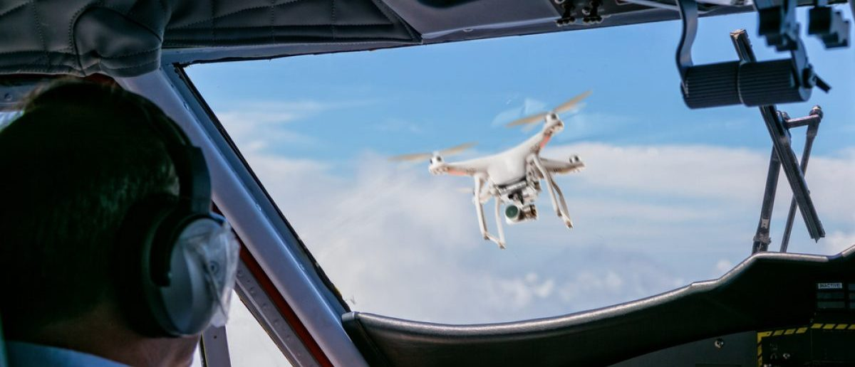 Pilot looking at a drone getting very close to a commercial airplane. [Shutterstock - Jag_cz]