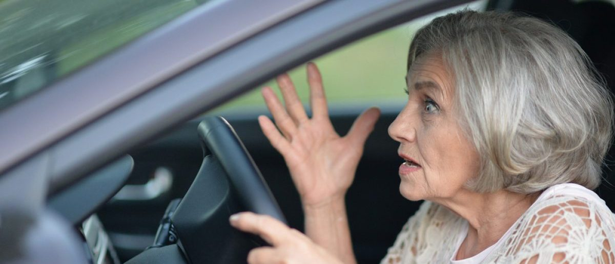 Shocked woman driving her car. [Shutterstock - Ruslan Guzov]