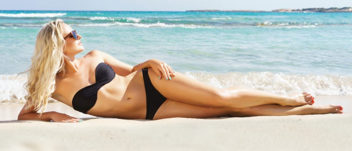 Blonde woman in a black bikini poses at the beach. Source: Shutterstock/