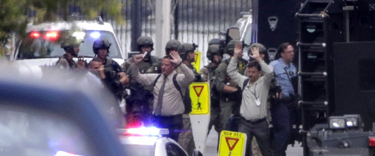 Evacuees raise their hands as they are escorted from the scene of a shooting at the Washington Navy Yard in Washington