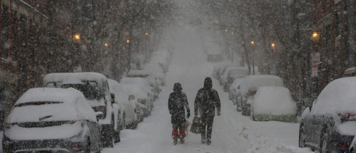 Pedestrians walk up a street on Beacon Hill during white-out, blizzard-like conditions in a winter nor'easter snow storm in Boston
