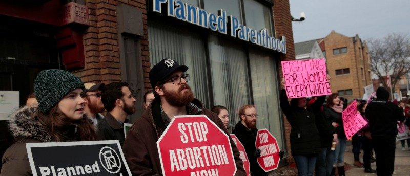 Pro-life activists (L) rally next to supporters of Planned Parenthood outside a Planned Parenthood clinic in Detroit, February 11, 2017. REUTERS/Rebecca Cook