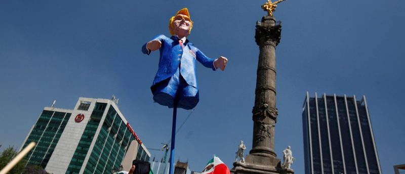A man holds up an effigy of U.S. President Donald Trump during a march to protest against Trump's proposed border wall and to call for unity, in Mexico City, Mexico, February 12, 2017. REUTERS/Jose Luis Gonzalez