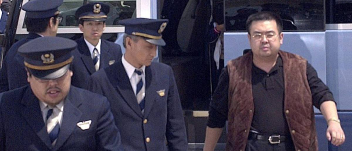 A man (R) believed to be North Korean heir-apparent Kim Jong Nam, is escorted by police as he boards a plane upon his deportation from Japan at Tokyo's Narita international airport in Narita, Japan, in this photo taken by Kyodo May 4, 2001. Picture taken May 4, 2001. Mandatory credit Kyodo/via REUTERS