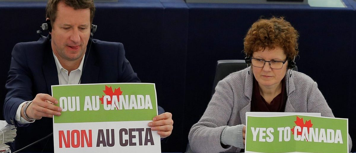 "French politician Yannick Jadot (L), green party EELV (Europe-Ecologie-les-Verts) candidate for the 2017 French presidential election and Member of the European Parliament sits behind a placard that reads ""Yes to Canada, No to CETA"" as he waits for the start of a voting session on the Comprehensive Economic Trade Agreement (CETA) between the EU and Canada, in Strasbourg, France, February 15, 2017. REUTERS/Vincent Kessler"