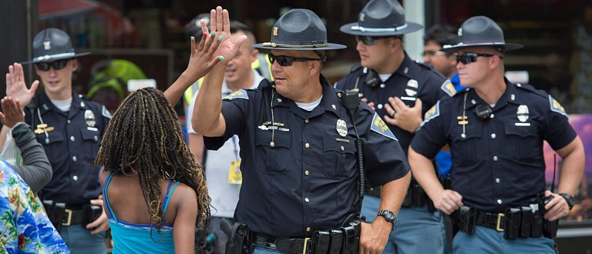 A woman gives a high-five to a police officer outside the Republican National Convention on July 18, 2016 in Cleveland, Ohio. Thousands of delegates descend on a tightly secured Cleveland arena for the opening of the Republican National Convention, with Donald Trump's wife playing character witness as the tough-talking mogul seeks to lock up his party's presidential nomination. (Photo credit: ANDREW CABALLERO-REYNOLDS/AFP/Getty Images)