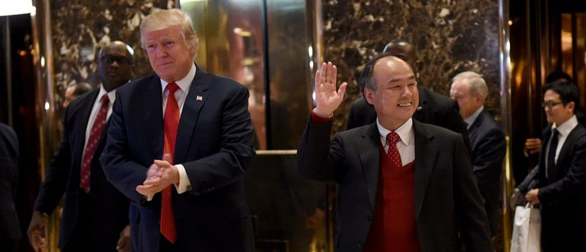 President-elect Donald Trump stands with SoftBank Group Corp. founder and Chief Executive Officer Masayoshi Son in the lobby of Trump Tower on December 6, 2016 in New York. (Photo credit: TIMOTHY A. CLARY/AFP/Getty Images)