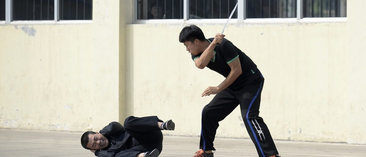A mock attacker (R) wields a prop knife at a man playing the role of a passenger during a drill aiming to enhance the police reaction of violent and terrorist attacks, at a railway station in Jinzhong, Shanxi province June 30, 2014. REUTERS/Jon Woo