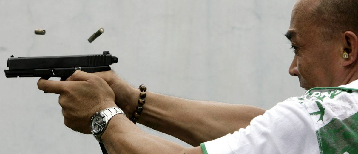 A policeman shoots at target at a firing range in Manila May 19, 2009. The Philippines, which has more gun-related deaths than any other country in Asia relative to its size, needs tougher gun control laws as the number of illegal weapons has topped one million, a police general said on Monday. REUTERS/Cheryl Ravelo
