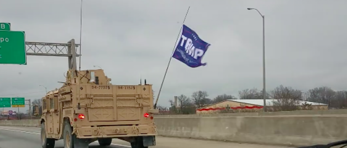 A Trump flag seen flying from a military convoy. (screenshot from public Facebook/Carole Puryear)