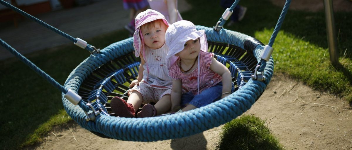 Toddlers enjoy a ride in a bed-swing in the outdoor area of the Kathinka-Platzhoff-Stiftung Kindergarten (Kathinka-Platzhoff-foundation kindergarden) in Hanau, 30km (18 miles) south of Frankfurt, July 16, 2013. From August 1, 2013, all children in Germany between the age of 1 and 3 will have a legal entitlement to a place at a kindergarten. The Kindergarten of the Kathinka-Platzhoff-Stiftung is one of few which hosts children between the age of six month and six years. Picture taken July 16. REUTERS/Kai Pfaffenbach