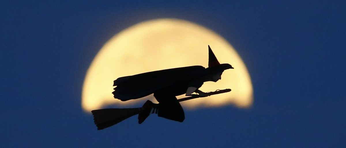 A radio-controlled flying witch makes a test flight past a moon setting into clouds along the pacific ocean in Carlsbad, California October 8, 2014. REUTERS/Mike Blake