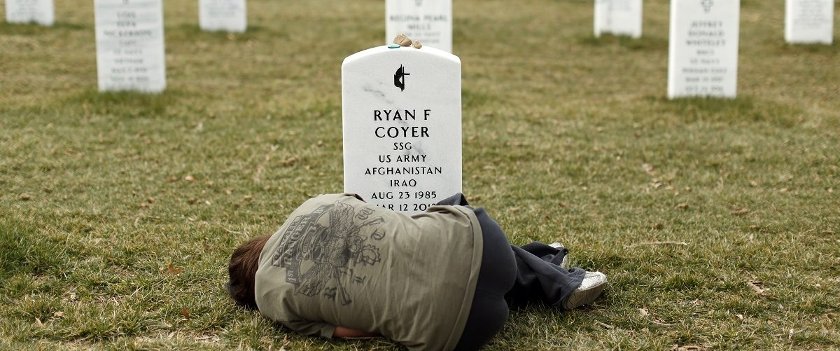 File photo of a woman lying down in front of the grave of her brother at Arlington National Cemetery near Washington