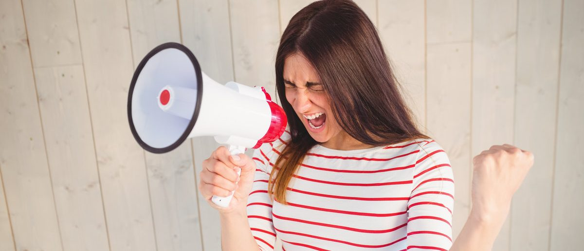 Pretty hipster shouting through megaphone on wooden planks background (Shutterstock/wavebreakmedia)